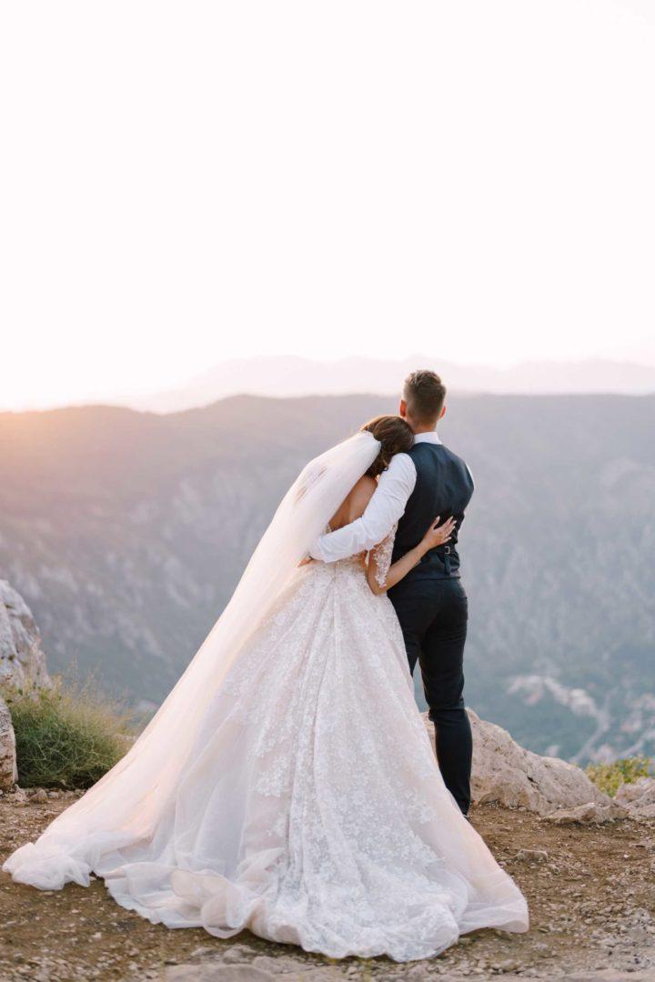Hochzeitspaar beim Ausblick auf die Berge im Ausland